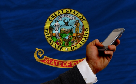telecommuniation: man holding cell phone in front flag of us state of idaho symbolizing mobile communication and telecommunication Stock Photo