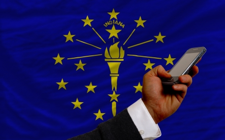 telecommuniation: man holding cell phone in front flag of us state of indiana symbolizing mobile communication and telecommunication