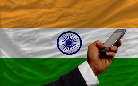 czÅ'owiek posiadajÄ…cy telefon komórkowy z przodu flagi narodowej Indii symbolizujÄ…cej mobilnÄ… komunikacjÄ™ i telekomunikacji Zdjęcie Seryjne