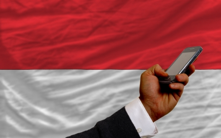 man holding cell phone in front national flag of indonesia symbolizing mobile communication and telecommunication