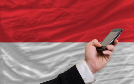 telecommuniation: man holding cell phone in front national flag of indonesia symbolizing mobile communication and telecommunication