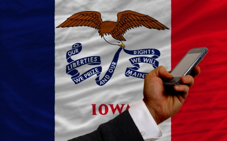 telecommuniation: man holding cell phone in front flag of us state of iowa symbolizing mobile communication and telecommunication