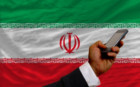 telecommuniation: man holding cell phone in front national flag of iran symbolizing mobile communication and telecommunication