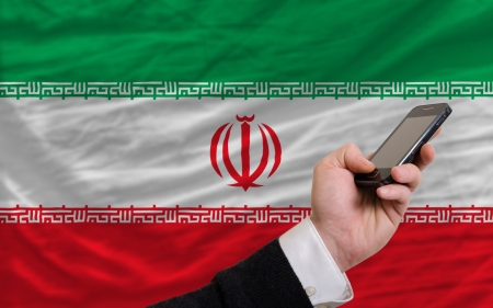 man holding cell phone in front national flag of iran symbolizing mobile communication and telecommunication
