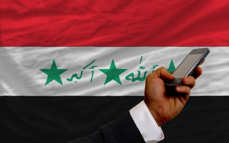 telecommuniation: man holding cell phone in front national flag of iraq symbolizing mobile communication and telecommunication