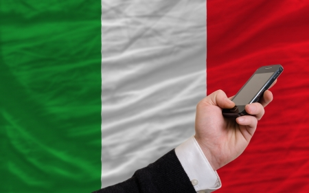 telecommuniation: man holding cell phone in front national flag of italy symbolizing mobile communication and telecommunication