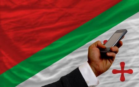 telecommuniation: man holding cell phone in front national flag of  katanga symbolizing mobile communication and telecommunication Stock Photo