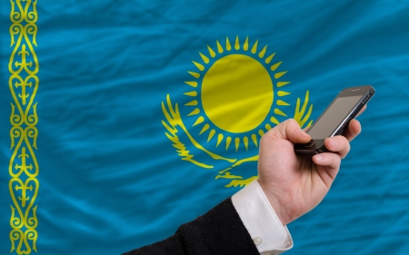 telecommuniation: man holding cell phone in front national flag of kazakhstan symbolizing mobile communication and telecommunication