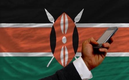 man holding cell phone in front national flag of kenya symbolizing mobile communication and telecommunication