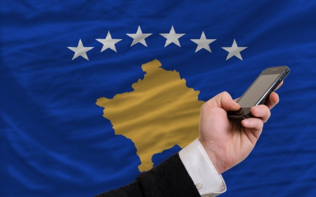 telecommuniation: man holding cell phone in front national flag of  kosovo symbolizing mobile communication and telecommunication