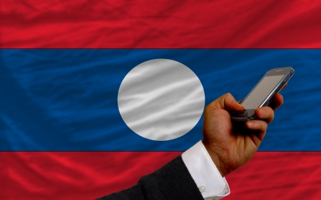 man holding cell phone in front national flag of laos symbolizing mobile communication and telecommunication Stock Photo - 17921419