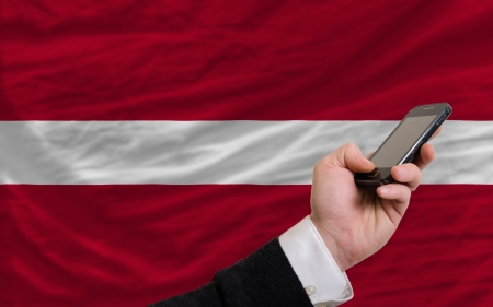 telecommuniation: man holding cell phone in front national flag of latvia symbolizing mobile communication and telecommunication