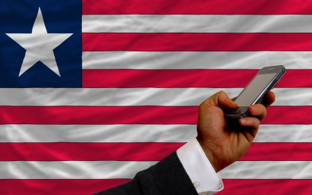 telecommuniation: man holding cell phone in front national flag of liberia symbolizing mobile communication and telecommunication Stock Photo