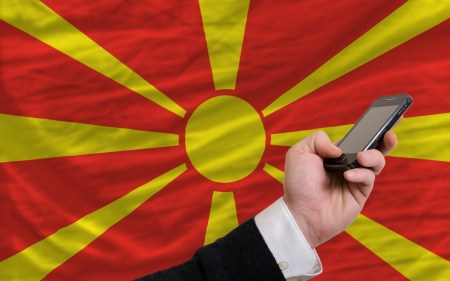 telecommuniation: man holding cell phone in front national flag of macedonia symbolizing mobile communication and telecommunication Stock Photo