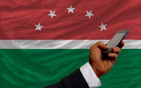 telecommuniation: man holding cell phone in front national flag of  maghreb symbolizing mobile communication and telecommunication