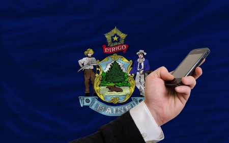 man holding cell phone in front flag of us state of maine symbolizing mobile communication and telecommunication