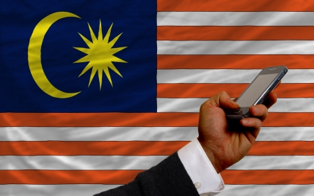 telecommuniation: man holding cell phone in front national flag of malaysia symbolizing mobile communication and telecommunication