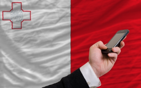 telecommuniation: man holding cell phone in front national flag of malta symbolizing mobile communication and telecommunication Stock Photo