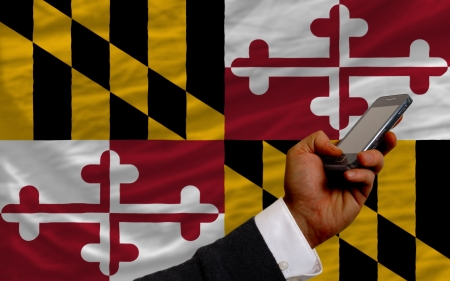 man holding cell phone in front flag of us state of maryland symbolizing mobile communication and telecommunication Stock Photo