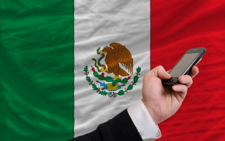 man holding cell phone in front national flag of mexico symbolizing mobile communication and telecommunication