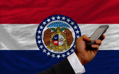 telecommuniation: man holding cell phone in front flag of us state of missouri symbolizing mobile communication and telecommunication
