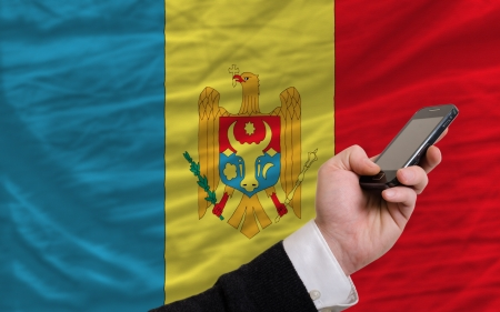 man holding cell phone in front national flag of moldova symbolizing mobile communication and telecommunication