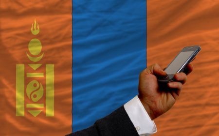 man holding cell phone in front national flag of mongolia symbolizing mobile communication and telecommunication