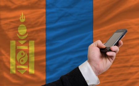 telecommuniation: man holding cell phone in front national flag of mongolia symbolizing mobile communication and telecommunication