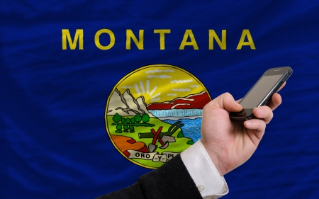 man holding cell phone in front flag of us state of montana symbolizing mobile communication and telecommunication