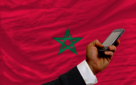 man holding cell phone in front national flag of morocco symbolizing mobile communication and telecommunication