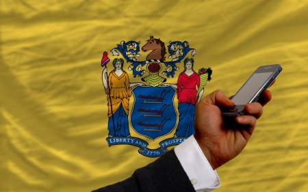telecommuniation: man holding cell phone in front flag of us state of new jersey symbolizing mobile communication and telecommunication