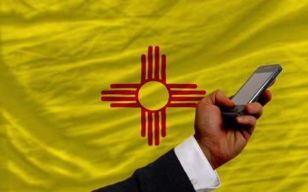 man holding cell phone in front flag of us state of new mexico symbolizing mobile communication and telecommunication