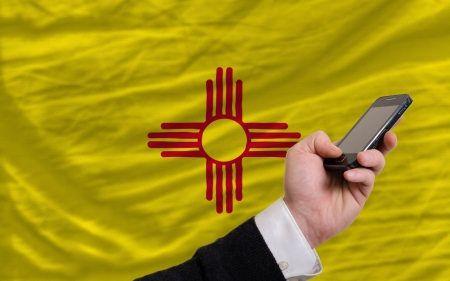 telecommuniation: man holding cell phone in front flag of us state of new mexico symbolizing mobile communication and telecommunication