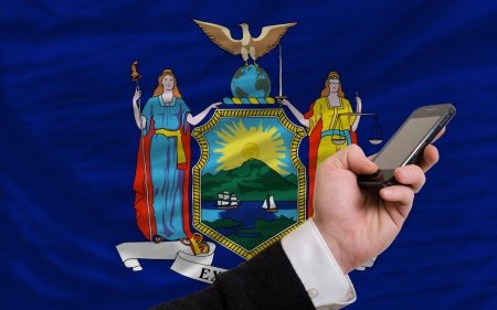 telecommuniation: man holding cell phone in front flag of us state of new york symbolizing mobile communication and telecommunication Stock Photo