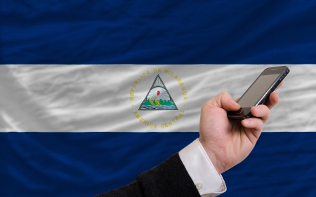 man holding cell phone in front national flag of nicaragua symbolizing mobile communication and telecommunication Stock Photo