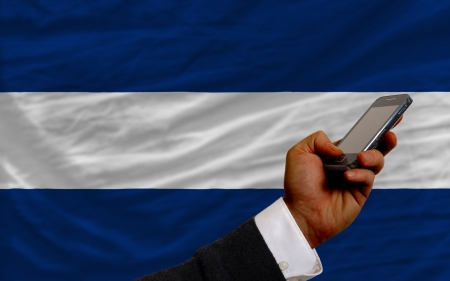 telecommuniation: man holding cell phone in front national flag of nicaragua symbolizing mobile communication and telecommunication Stock Photo