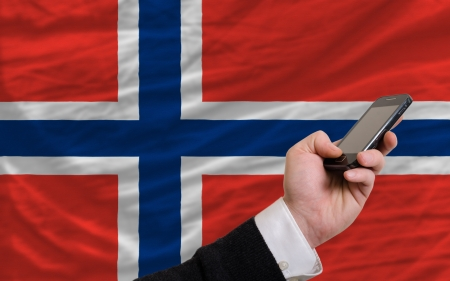 man holding cell phone in front national flag of norway symbolizing mobile communication and telecommunication Stock Photo