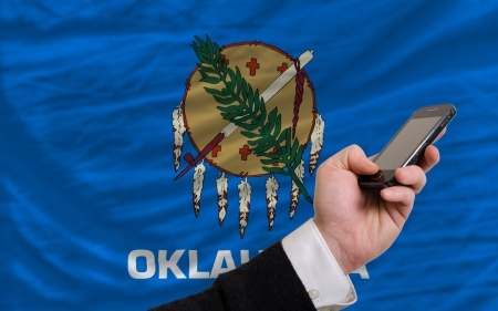man holding cell phone in front flag of us state of oklahoma symbolizing mobile communication and telecommunication Stock Photo