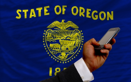 man holding cell phone in front flag of us state of oregon symbolizing mobile communication and telecommunication Stock Photo