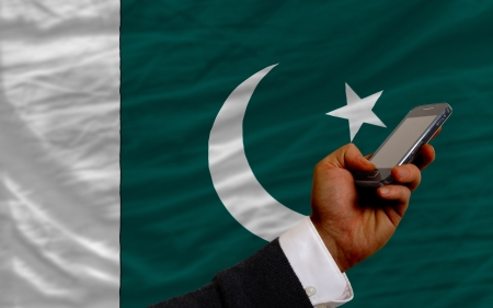 telecommuniation: man holding cell phone in front national flag of pakistan symbolizing mobile communication and telecommunication Stock Photo