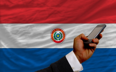 telecommuniation: man holding cell phone in front national flag of paraguay symbolizing mobile communication and telecommunication Stock Photo