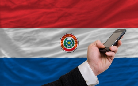 man holding cell phone in front national flag of paraguay symbolizing mobile communication and telecommunication Stock Photo