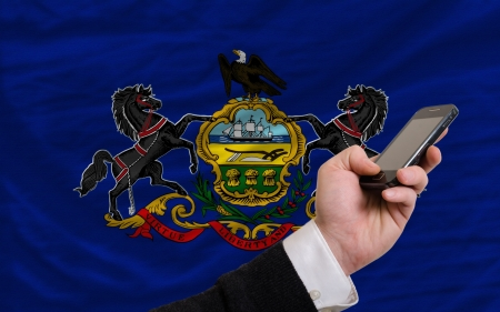 telecommuniation: man holding cell phone in front flag of us state of pennsylvania symbolizing mobile communication and telecommunication