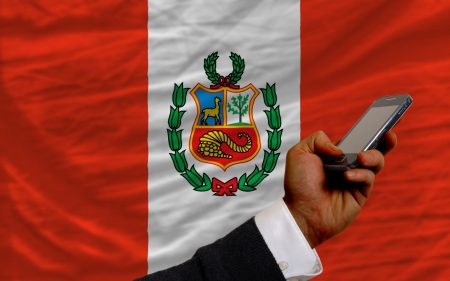 telecommuniation: man holding cell phone in front national flag of peru symbolizing mobile communication and telecommunication