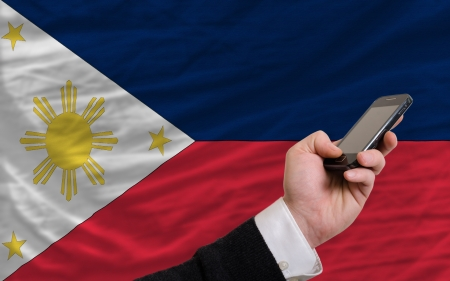man holding cell phone in front national flag of philippines symbolizing mobile communication and telecommunication Stock Photo