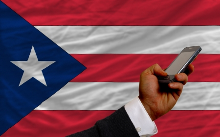 puertorico: man holding cell phone in front national flag of puertorico symbolizing mobile communication and telecommunication