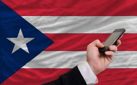 puerto rican flag: man holding cell phone in front national flag of puertorico symbolizing mobile communication and telecommunication
