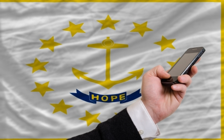 man holding cell phone in front flag of us state of rhode island symbolizing mobile communication and telecommunication Stock Photo