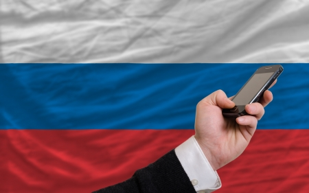 telecommuniation: man holding cell phone in front national flag of russia symbolizing mobile communication and telecommunication