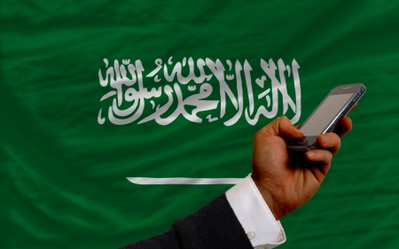 telecommuniation: man holding cell phone in front national flag of  saudi arabia symbolizing mobile communication and telecommunication